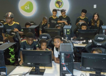 Em frente a computadores, jovens e crianças do projeto jogam durante a aula. Os meninos, que são maioria, são negros. No fundo, uma menina também participa da atividade.
