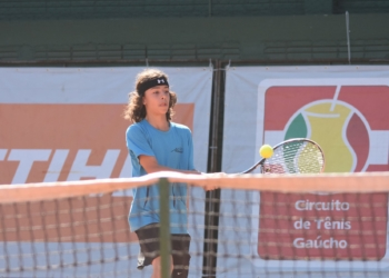 Através da rede de tênis vê-se o tenista rebater a bola com sua raquete. Ao fundo se lê Circuito de Tênis Gaúcho e há a marca de um patrocinador
