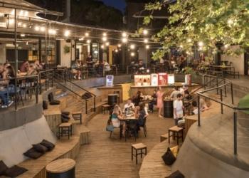 Uma praça de alimentação com pessoas sentadas, um ambiente mais alto, com lojas em volta, e outro mais baixo, simulando uma pista de skate, onde há mais mesas e pessoas.