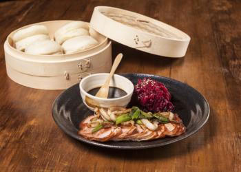 Prato picanha suína com potinho de molho e pães em outro recipiente.