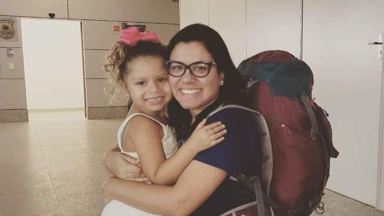 Uma criança e uma mulher abraçadas, mãe e filha. A mãe carrega uma mochila de viagem.