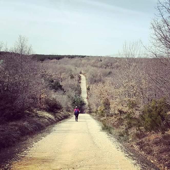 Ao longe, vê-se uma pessoa em uma estrada, com boa parte percorrida e um longo caminho ainda ao longe.