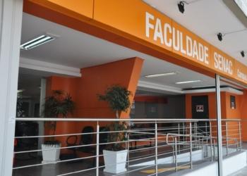 Faculdade Senac, vê-se rampa de acesso, piso tátil, cadeiras e plantas decorativas na entrada