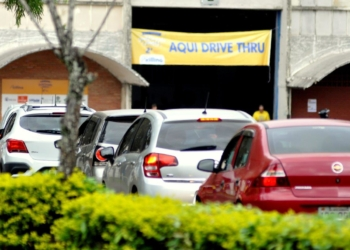 """Fila de carros em direção a uma faixa onde diz """"aqui drive thru"""""""