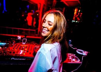 A DJ Mari Hermel, em frente a uma mesa de som, em um ambiente de luz avermelhada.