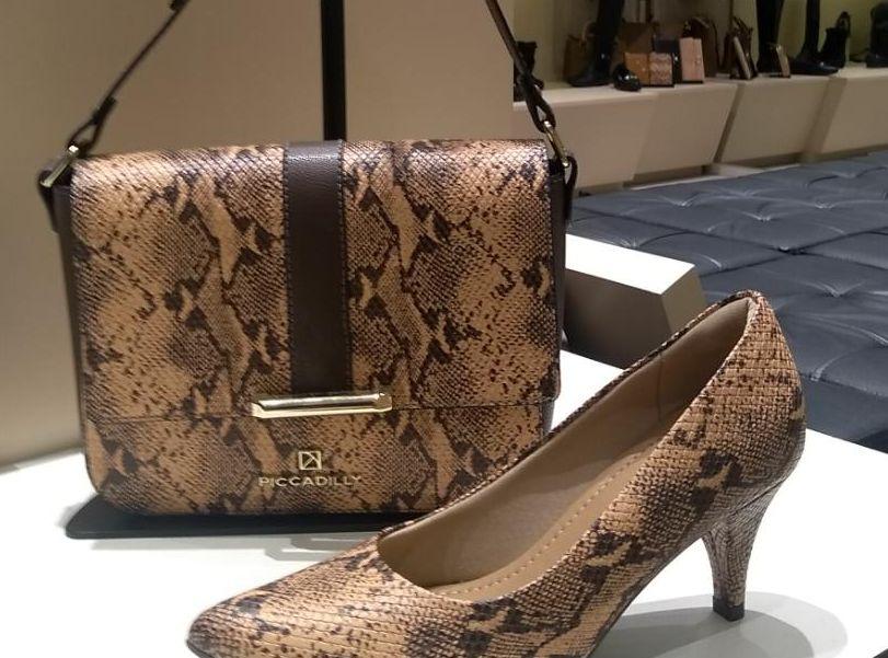 Sapato e bolsa de couro em vitrine, com mais bolsas ao fundo.