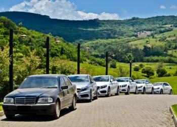 Diversos carros, um atrás do outro. Atrás uma paisagem natural, muito verde.