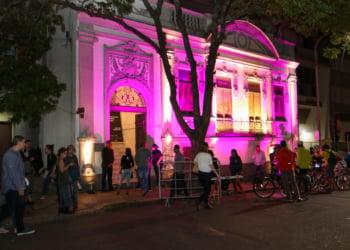 À noite, diversas pessoas se concentram em frente a um prédio antigo, iluminado, em tons de rosa.