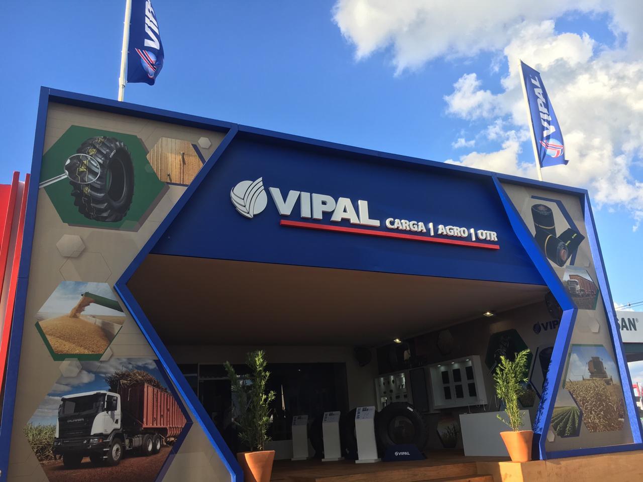 Estande da Vipal no evento, com pneus do lado de dentro, fotos aplicadas no estande com produtos da marca e duas bandeiras da marca no topo