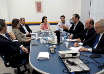 Uma mesa de reuniões com diversas pessoas em volta.