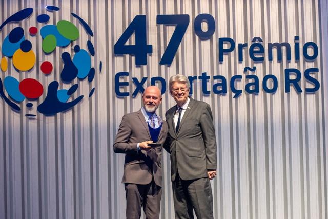 Dois homens de terno apertam as mãos em frente a letreiro 47º Prêmio Exportação