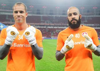 Dois goleiros, com fardamento em cor laranja, dentro do estádio, mostram as luvas com a hashtag da campanha.