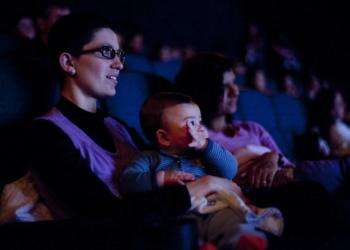 Uma mulher, de óculos, com uma criança pequena no colo, olha para um local iluminado - é um cinema. Atrás deles é possível ver outra mulher com um pacote de pipoca.