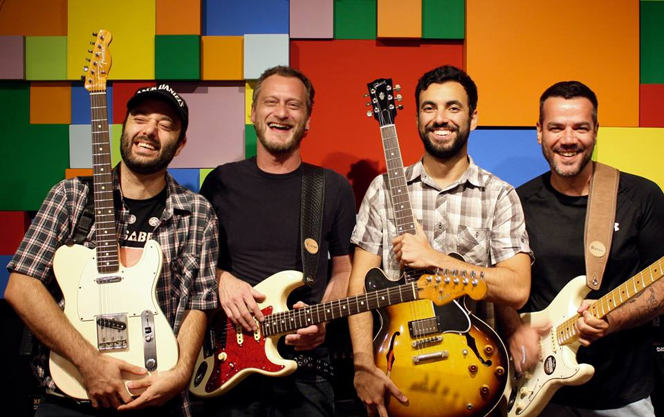Quatro homens com guitarras sorriem em frente a uma parede com quadrados coloridos.