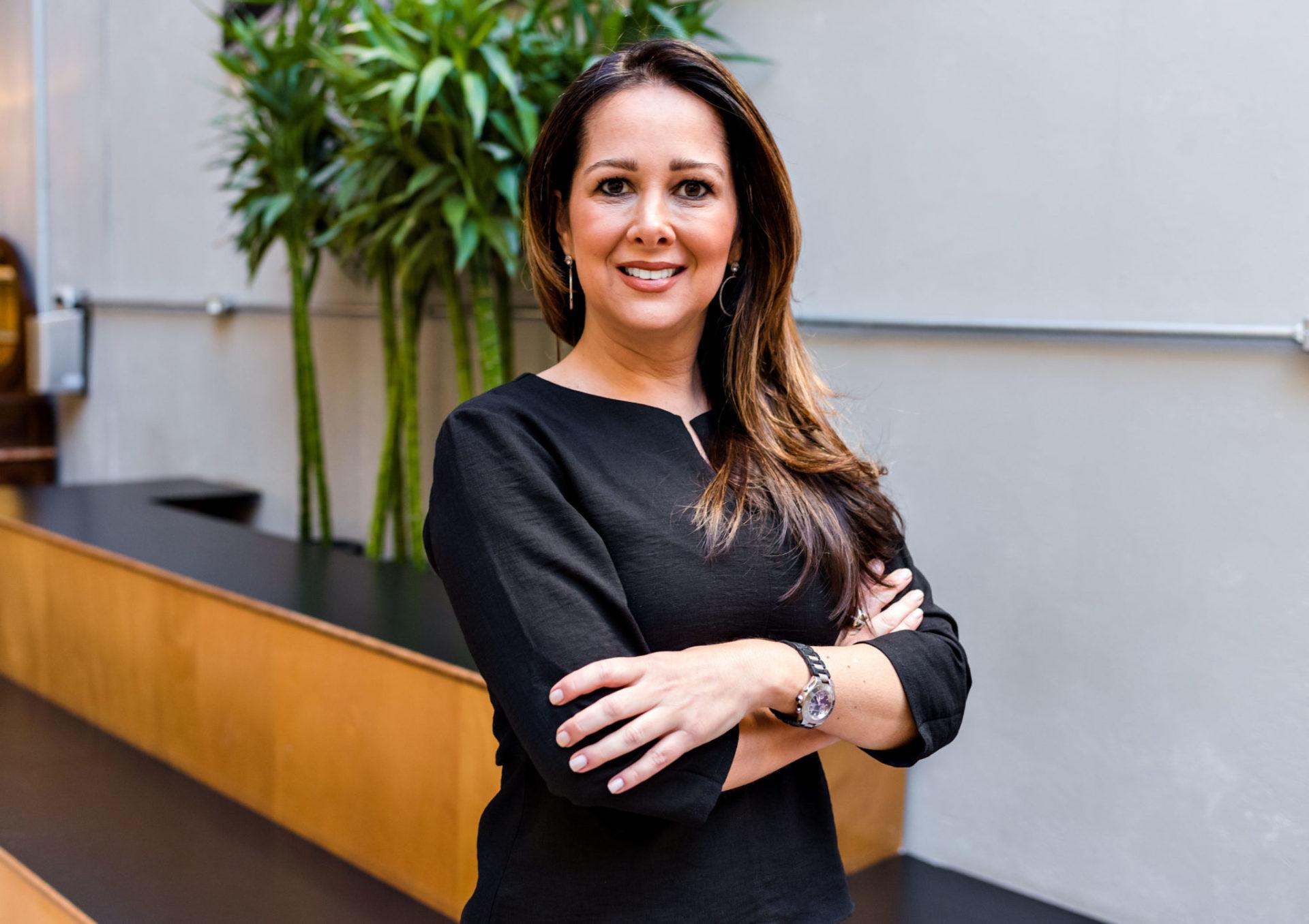 Uma mulher vestindo preto sorri, de braços cruzados, em frente a um local com uma folhagem atrás.