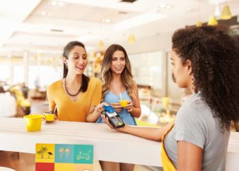Duas mulheres apresentam a uma balconista o cartão para uso na maquininha.