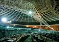 Auditório com centenas de cadeiras vazias. Acima vê-se a estrutura do teto.