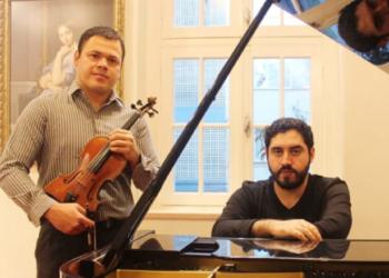 Dois homens, um debruçado em um piano e outro com um violino.