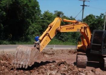 Máquina revolve chão durante obra em estrada.