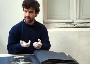 Um homem usa luvas para manuseio de um livro-álbum, com folhas pretas e fotografias.
