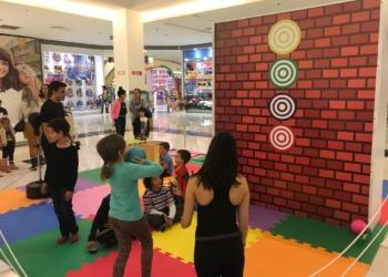 Crianças brincam de tiro ao alvo com uma bola em um espaço colorido.