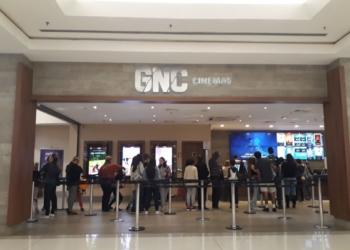 Frente do cinema com pessoas na entrada e esperando para comprar ingressos.