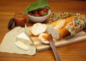 Embalagens podem ser usadas para embalar alimentos diversos, como pães, na foto em cima de uma tábua de madeira, queijos ou frutas. Na foto, pão, queijo, geleia e um pote de morangos.