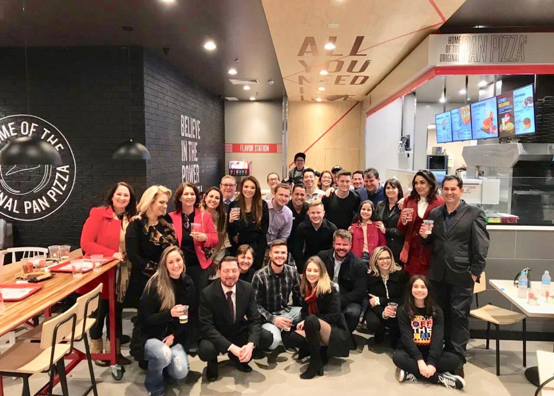 Diversas pessoas reunidas posam para foto na pizzaria.