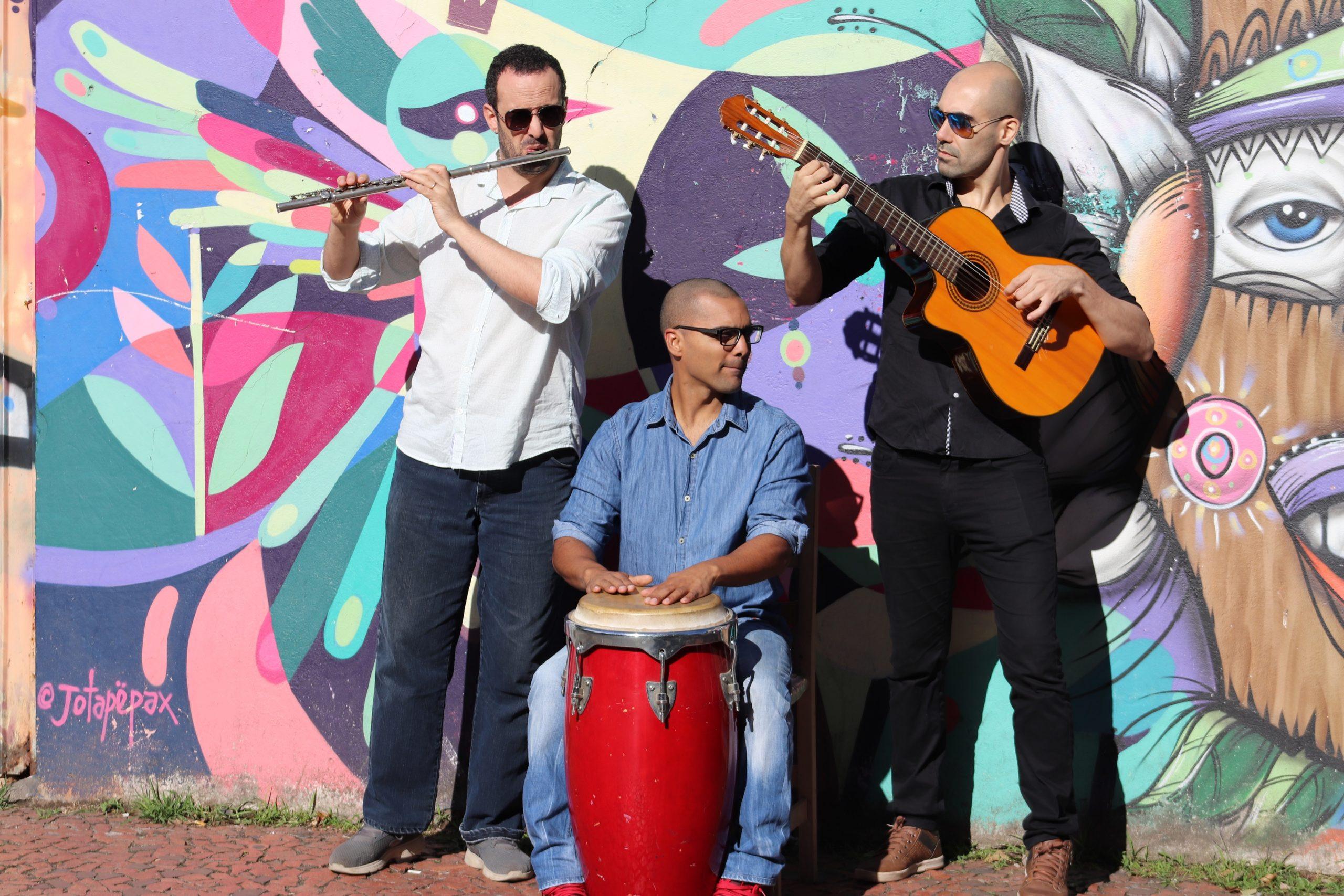 Fiesta latina: três homens, um com violão, outro com flauta, ambos em pé, atrás um muro colorido. Sentado, um homem na percussão.