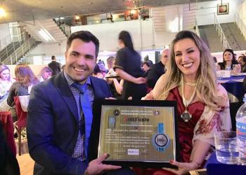 Tânia Zambon recebeu prêmio em SP. Na foto, um homem e uma mulher seguram uma placa.