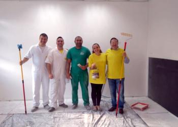 Kinder e Killing. Cinco pessoas, quatro homens e uma mulher, em um espaço branco, com pincéis e rolos de pintar. O chão está forrado. Os dois primeiros vestem macacões brancos, o do meio veste verde e os dois últimos vestem camisetas amarelas.