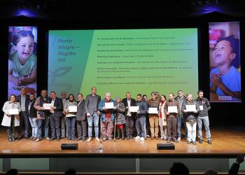 Diversas pessoas com uma espécie de certificado em um palco com um telão atrás.