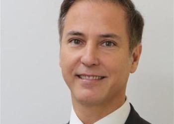 LIDE. Um homem posa sorrindo para a foto usando terno e gravata.