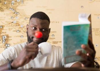Na Vida Real Bar. Um homem negro usa um nariz vermelho de palhaço e segura, com uma mão, uma xícara, na outra, um livro.