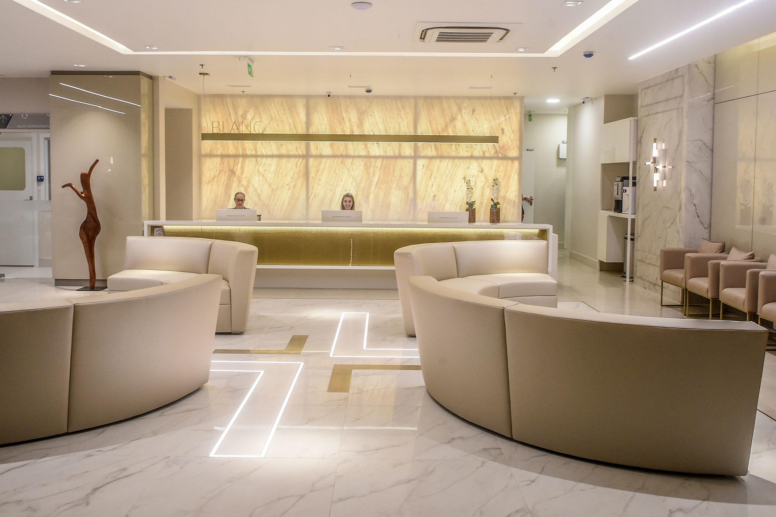 Blanc Hospital. Espaço interno com recepção, sofás e cadeiras.