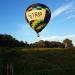 """Balonismo. Um balão colorido com a inscrição """"trip"""" sobrevoa um campo em um dia de céu azul."""