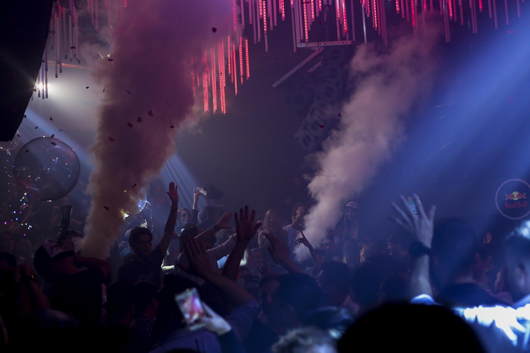 Provocateur. Ambiente noturno, escuro, luzes e fumaça. Vê-se as mãos das pessoas para cima, alguns rostos ao fundo.
