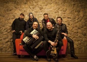 Rock de Galpão. Seis homens em frente a uma parede de pedra, dois deles sentados em um sofá vermelho, os outros ao redor. Os que estão sentados carregam acordeon e guitarra.
