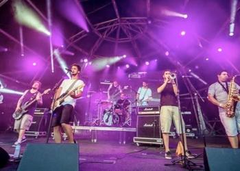 Second Hand. Uma banda toca em um palco iluminado com cor predominantemente púrpura.