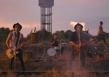 Stones Blues Band. Em um espaço semelhante a uma fábrica abandonada, com grama crescendo e terra ou brita, três homens tocam, dois à frente com baixo e guitarra, outro atrás a bateria e outro mais atrás carrega instrumento de corda ainda na caixa. Vê-se fogo atrás e no canto esquerdo.