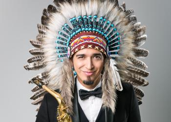 Vini Netto. Um homem usando smoking e um cocar de índio estilo americano segura um saxofone