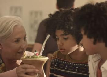 Uma senhora branca alcança uma cuia de chimarrão para dois meninos negros