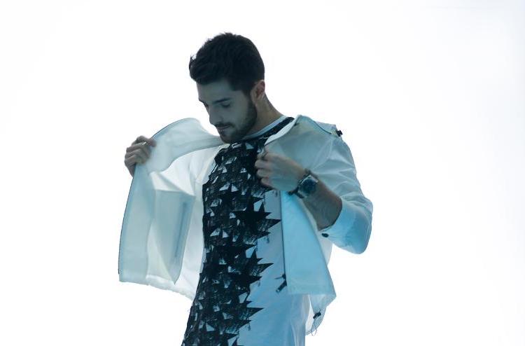 Alok. Um homem abre jaqueta branca, olhando para baixo. Atrás um fundo branco.