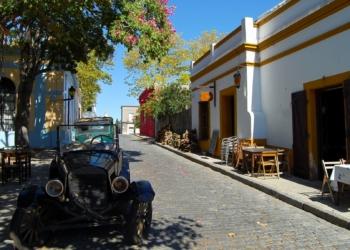 Rua de Colonia do Sacramento, no Uruguai, com mesinhas do lado de fora de prédios e um carro antigo estacionado embaixo de uma árvore