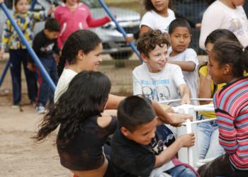 Pracinha. Crianças brincam em brinquedo de girar em pracinha.