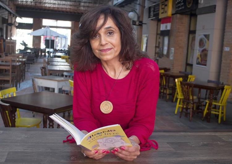 Laura Dutra. Uma mulher usando uma blusa rosa e um colar com pingente em círculo segura o livro de sua autoria.