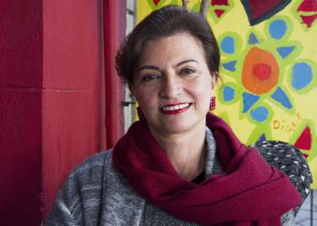 Monalisa no retrovisor é de autoria de Lisana Bertussi. Uma mulher usa um cachecol e sorri para a câmera. Atrás um fundo colorido.