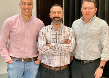 Telefonia móvel. Três homens, o do centro com os braços cruzados, posam para a foto.