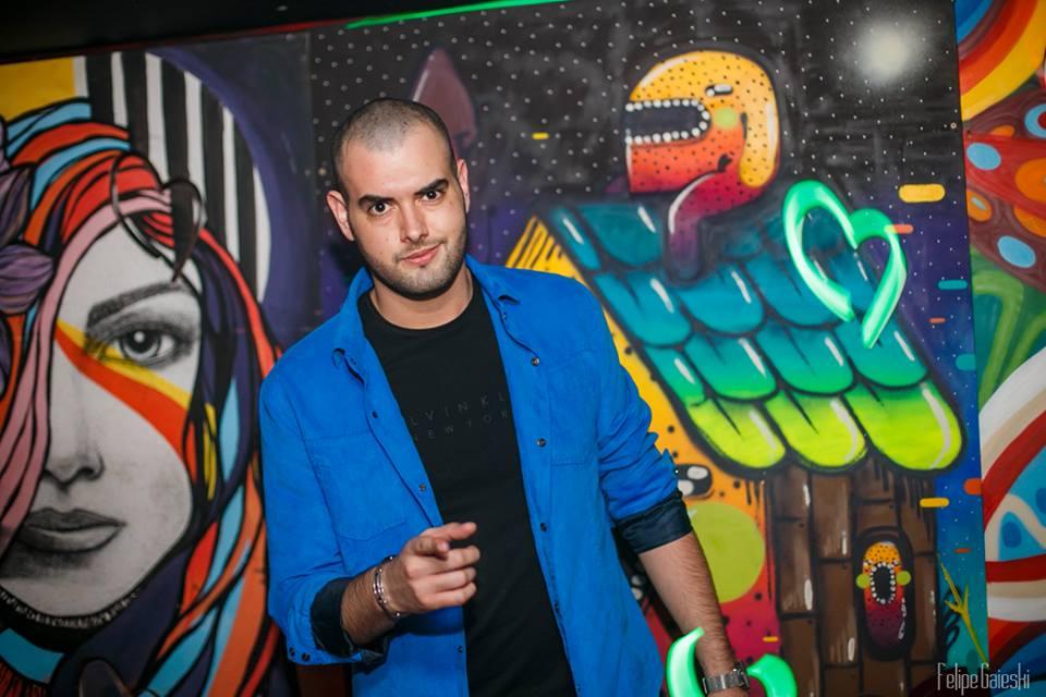 The Party Never Ends com Vini Leonel. Uma homem de blusa preta e terno azul em frente a um painel colorido aponta para o espectador.