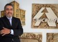 Presidente da Unicred colabora com Faculdade de Medicina. Um homem de terno e braços cruzados sorri em frente a uma imagem de prédio histórico e outra com o nome da Unicred e logomarca.